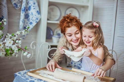 Young mother with her little daughter sculpt a dough